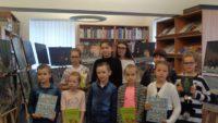 """Wszyscy uczestnicy konkursu """"Planszówka"""" pozują do zdjęcia grupowego z książkami/nagrodami w dłoniach."""