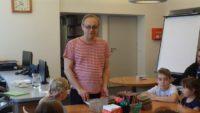 Daniel de Latour, stoi przed słuchaczami siedzącymi przy stole roboczym.