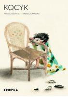 """Okładka książki """"Kocyk"""" Miguela Gouveia. Na kremowym tle okładki znajduje się duży wiklinowy fotel. Obok niego stoi chłopiec z narzuconym na plecy kocykiem. Przed fotelem stoją 4 modele aut osobowych. Chłopiec trzyma piąty w dłoni i wprawia go w ruch na poręczy fotela."""